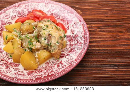 oven baked chicken fillet with potatoes and rosemary on woden table