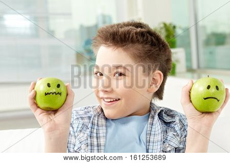 Portrait of smiling boy holding apples with smiley faces