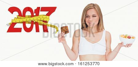 3D Woman with fruit bowl making faces as she looks at cookie against digitally generated image of new year with tape measure