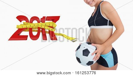3D Portrait of happy woman in sportswear with football against new year with tape measure