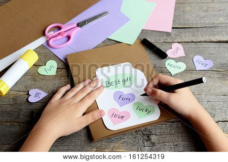 Kid doing a greeting card. Kid holds a black marker in hand and writes wishes. Paper greeting card with jar, hearts and wishes. Scissors, colored paper set, glue stick on wood table. Children activity