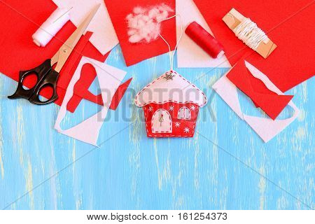 Christmas house decor sewn from red and white felt, scissors, felt sheets and scraps, needle, thread spool, filler on a blue wooden background with copy space for text. Christmas DIY concept. Top view