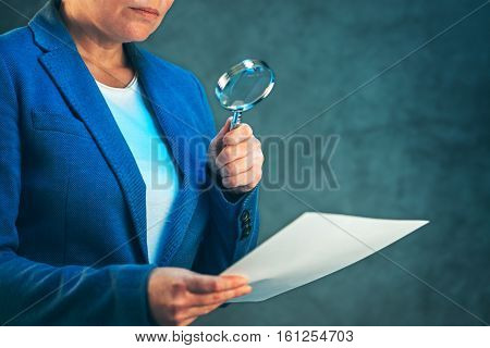 Female lawyer reading legal contract agreement disclaimer with magnifying glass company's legal representative working