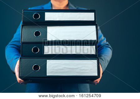Business woman holding document binders with archived paperwork and other corporate legal sheets mock up copy space