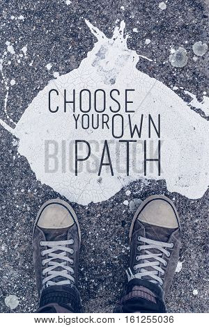 Choose your own path motivational quote on urban asphalt background with young male feet wearing sneakers top view.