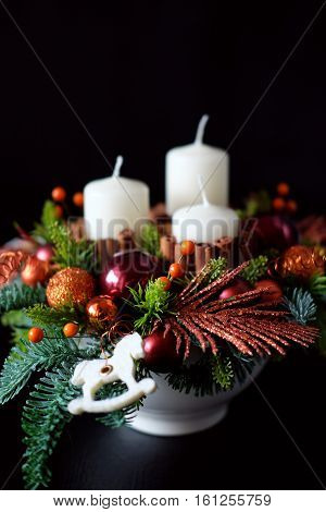 Winter table centerpiece wreath with candles new year toys spice and fir branches