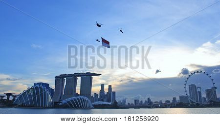 Marina Bay, Singapore - July 21, 2012: The flypast of the Singapore flag during the National Day Parade 2012. Flag is carried by a Chinook CH-47 transport helicopter escorted by 2 Apache AH-64 attack helicopters.