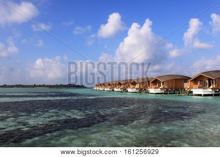 Finolhu, Maldives - January 27, 2015: A row of luxurious overwater villas in the Maldives. Offering sunrise views and direct access into the Indian Ocean. Photo taken on a day with near perfect blue skies and clouds