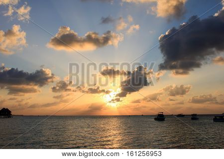 Finolhu, Maldives - January 27, 2015: Nature`s daily lightshow as seen in the Maldives. Sun setting against silhouettes of clouds and boats