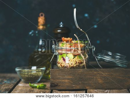 Homemade jar quinoa salad with cherry tomatoes and sun-dried tomatoes, avocado, basil. Detox, dieting, vegetarian, vegan, clean eating food concept. Dark blue background, selective focus, copy space