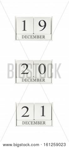 Closeup group of white wooden calendar with black 19 20 21 december word three date calendar isolated on white background