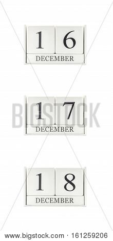 Closeup group of white wooden calendar with black 16 17 18 december word three date calendar isolated on white background
