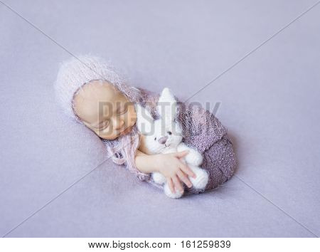 swaddled sleeping newborn girl with white toy in hand