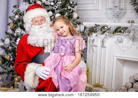 Santa Claus sitting with a little girl dressed in a beautiful dress. Christmas scene. Family celebration.