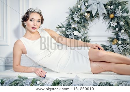 Christmas, fashion concept. Beautiful charming woman in evening dress and tiara lying on a fireplace in luxurious apartments decorated for Christmas. Beauty, fashion.