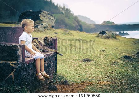 Child and dog are sitting on a bench and looking sea