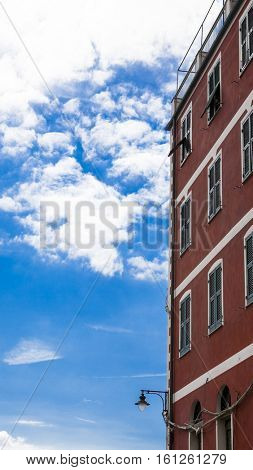 Old red wall of the house from the street lamp against the blue sky with white clouds. Italy. A good place for romantic walks.