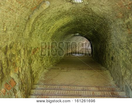 Picture of the brick down stairs to the tunnel with walls made of stone. Background of the tunnel with grey green stone walls texture.