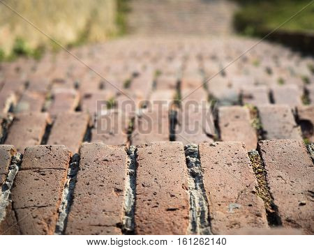 Selective soft focus on an old red brick down stairs. Background of the old brick down stairs close up. Brick down stairs pattern closeup.
