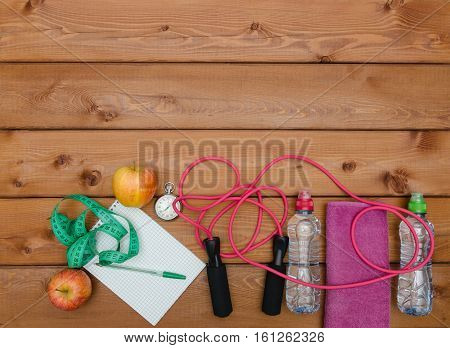 Bottle with towel apple skipping rope stopwatch and measuring tape on wooden table background. Fitness lifestyle concept.