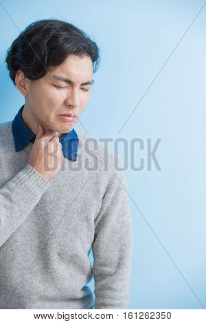 man student feel sore throat with blue background asian