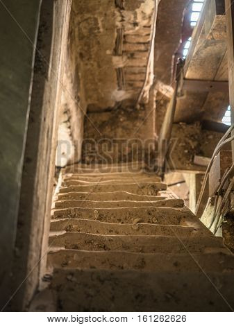 Picture of the old wooden down stairs in the belfry. Wooden stairs opposite the molder wall of the church. The sunlight shining feebly through the slit between red planks..