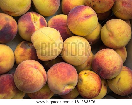 Background of a stacked yellow red peaches close up. Yellow peaches pattern on sale at the market.