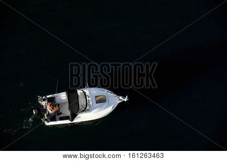 Man fishing from a small boat with an outboard motor. View from above. Little Belt in Denmark.