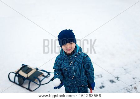 Cute five years old boy playing on winter forest