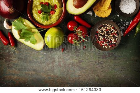 Bowl of Traditional latinamerican mexican sauce guacamole with fresh ingredients on dark rustic background. Top view