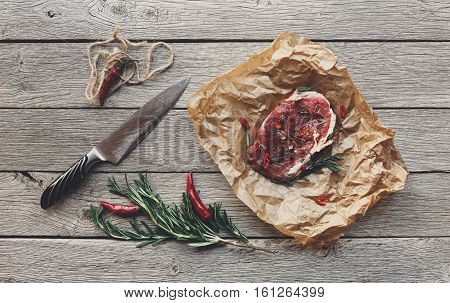 Raw beef steak in craft paper on dark wooden table background, top view. Fresh juicy meat, knife, rosemary and chili peppers. Cooking ingredients, butcher's and grocery concept, filtered