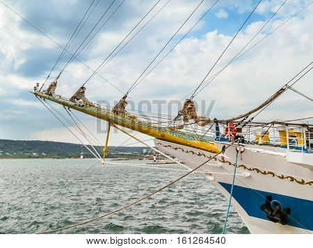 Bowsprit of the ancient sailing ship on the cloudy sky background
