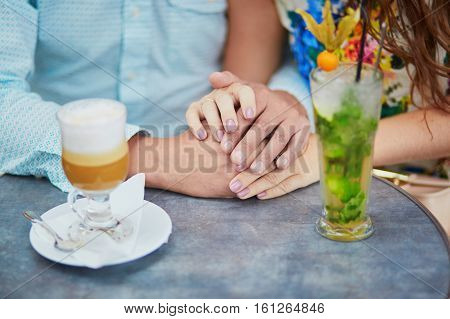Romantic couple having a date in Parisian cafe. Closeup of man and woman hands coffee and glass with mint cocktail