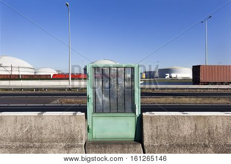 Roadblock with a green door with damaged safety glass near storage tanks in the port of Rotterdam