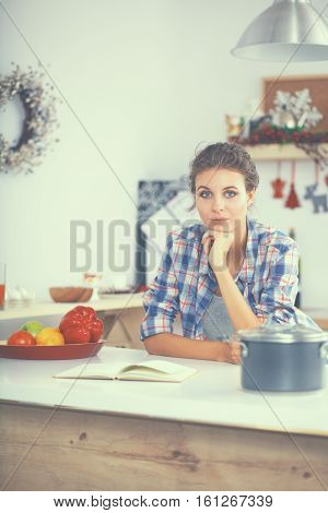 Young woman reading cookbook in the kitchen, looking for recipe.