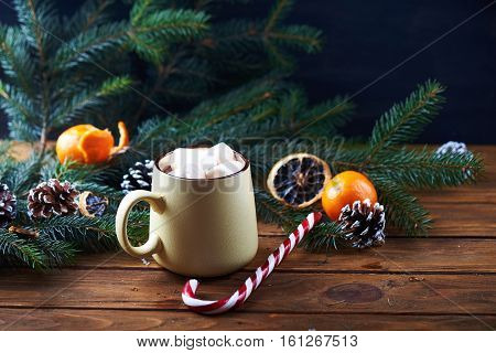 mug with hot chocolate, christmas tree, tangerines, peppermint stick and marshmallow on a wooden background. Dark photo. Empty space for text