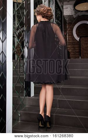 Beautiful Young Girl Model Is Back In A Black Dress On A Background Of A Wall Mirror, Makeup