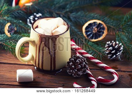 Close view at mug with hot chocolate with dripping chocolate, christmas tree, tangerines, peppermint stick and marshmallow on a wooden background. Dark photo. Toned for art effect