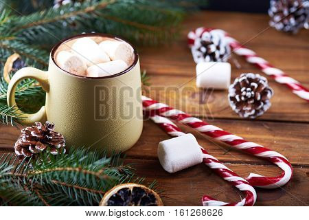 Close view at mug with hot chocolate, christmas tree, tangerines, peppermint stick and marshmallow on a wooden background. Dark photo. Empty space for text