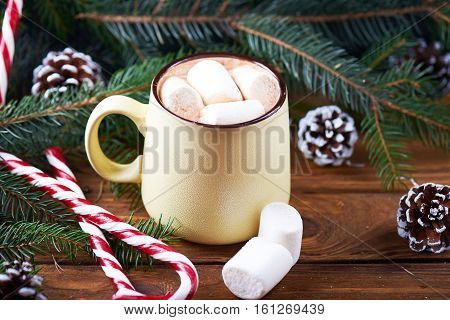 Close view at mug with hot chocolate, christmas tree, tangerines, peppermint stick and marshmallow on a wooden background. Dark photo.