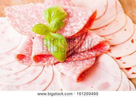 Cutting sausage and cold salami slices close up