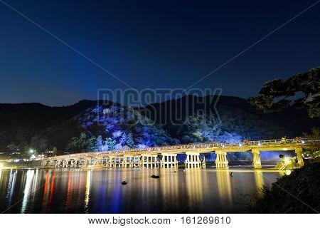 Togetsu Bridge reflecting in the Katsura River at night during the December illumination festival in the Arashiyama area of Kyoto