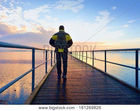 Man Hiker Walk On Wet Mole Above Sea To Sun. Fantastic Morning