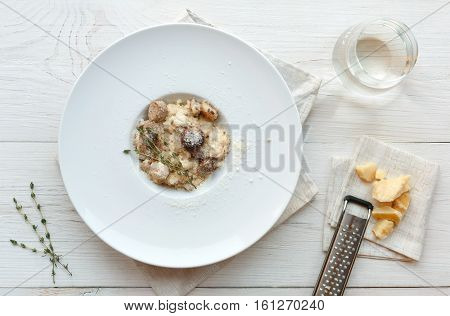 Wild mushrooms porcini risotto with rosemary and fresh grated parmesan cheese. Traditional italian cuisine dish. Restaurant food closeup. Forest fungus with rice. Top view, vertical composition