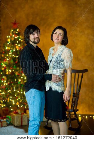Nice young couple stands near the Christmas tree. The young man gently embraces the girlfriend. The woman is elegantly dressed. The Christmas tree is festively decorated.