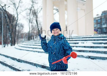 Little boy playing in the snow, in park