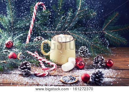mug with hot chocolate, christmas tree, tangerines, peppermint stick and marshmallow on a snow wooden background with falling snow. Dark photo. Empty space for text. Toned for art effect