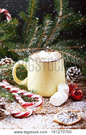 mug with hot chocolate, christmas tree, tangerines, peppermint stick and marshmallow on a snow wooden background with falling snow. Dark photo. Vertical shot