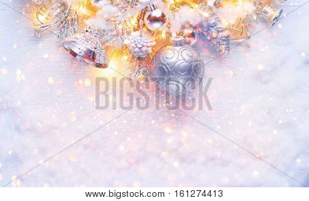 Christmas and New Year Decoration over white wood background. Border art design with holiday baubles. Beautiful Christmas tree closeup decorated with ball, holly berry, tinsel. Pastel colors, vintage