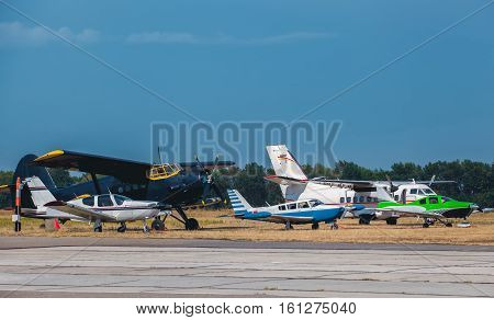 Five small aircraft next to each other are at the airport before take-off.